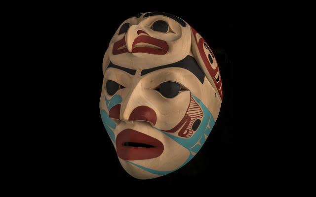 Máscara de bailarin de colores rojo, negro y azul con un adorno con forma de halcón en su parte superior, es tallada en madera por Dempsey Bob, indígena canadiense