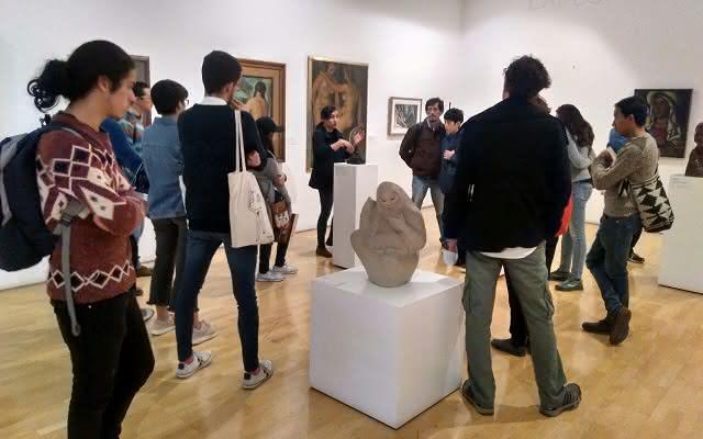 Personas reunidas en torno a una guia en una sala del Museo MAMU