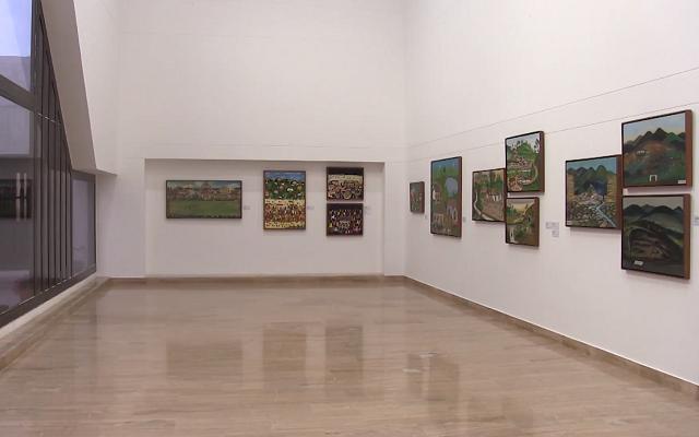 Sala de exposiciones con varias pinturas de la exposición aparente ingenuidad